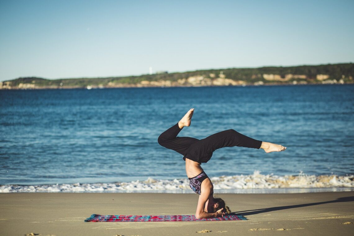 Frau macht Yoga am Strand